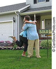 Sold! - Couple hugging outside of newly purchased house