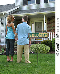Bought the house! - Couple outside of newly purchased house