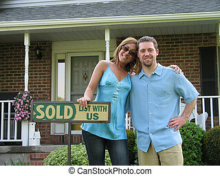 house shopping - Couple outside of newly purchased house