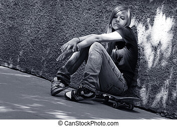 Sad angel - The girl with skateboard sitting against a wall....