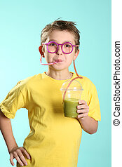 Health drink - A boy sips a healthy juice containing wheat...