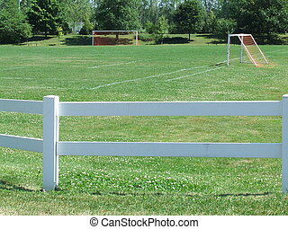 soccer field - a soccer field with a white rail fence...