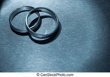 Wedding Rings - A pair of wedding bands against a textured...