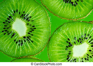 Kiwi slices on green background