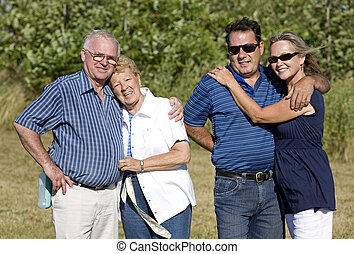 two generations - happy two older couples posing in the...
