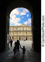 Louvre - Mother and children entering Louvre in Paris,...