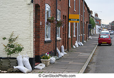 Flood warning - Sandbags on doorsteps in a small English...