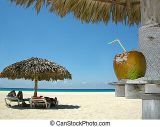 tropical beach - people relaxing under tropical huts with...