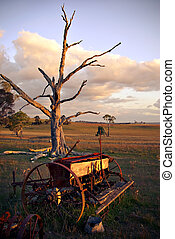 old plough on farm at sunset