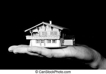property market - a man is holding a house in his hand -...
