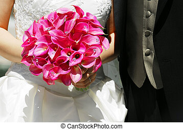 Bride and groom. Closeup on wedding bouquet.