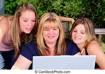 Family Computer - Mother And Two Daughters Outdoors On The...