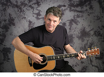 Mature Male Guitarist - A handsome, mature musician playing...