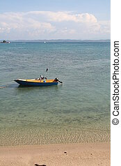 Beach boat - Small engined boat in the ocean next to beach