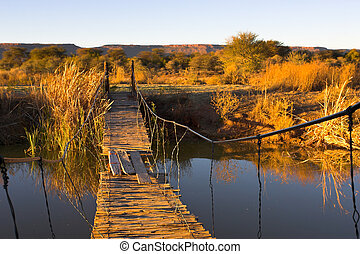 Rope bridge leading across a river to a small island.
