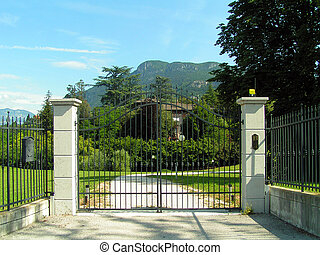 Closed gates to a private property: meadow and a manor are...