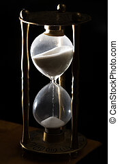 Sands of time - Brass hour glass on black with top sands lit...
