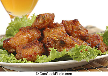 Chicken Wings - Closeup of barbecued chicken wings on a bed...