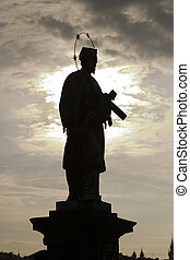 Saint Silhouette - A statue of a saint with a copper halo on...