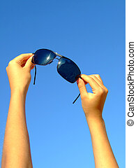 Female hands hold sunglasses on a background of the blue sky