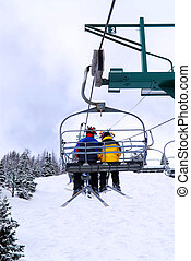 Skiers on chairlift - Skiers wearing funny hats on a...