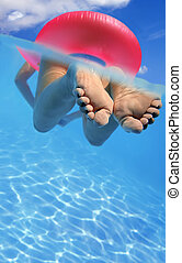 Woman in Pool - Woman floating in rubber ring in blue...