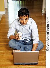 Businessman at home - An asian businessman sitting on the...