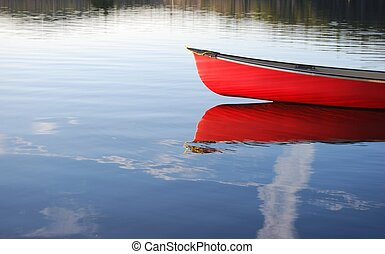Red Canoe - red canoe reflects in water of lake near...