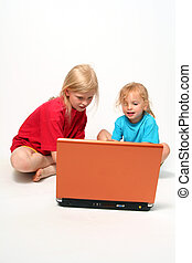 Playing on laptop - Two little girls playing on laptop on a...
