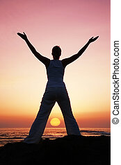 Sunset Yoga - Woman in meditation pose at sunset with...