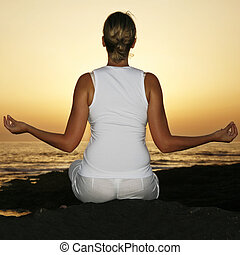 Sunset Yoga - Woman in meditation pose at sunset with fill...