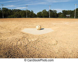 Home plate on a baseball field with a baseball set on it