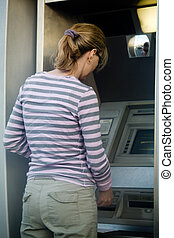 Woman banking - Woman outside using an automated bank...