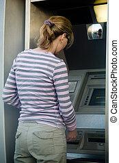 Woman banking - Woman outside using an automated bank...