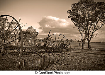plough in sepia - an old plow lay forgotten and neglected in...