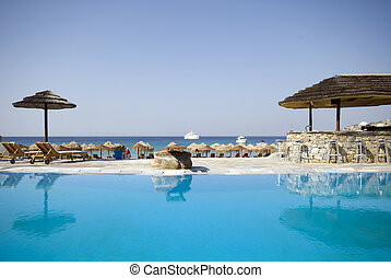 pool at greek island resort - swimming pool by sea at resort...