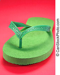 flip flops - green plastic flip flops against colored...