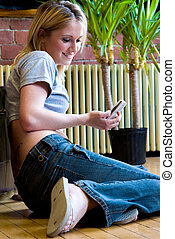 Checking messages on cellphone - A woman checks her SMS...