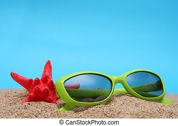 Sunglasses - Green sunglasses and sand on a blue background