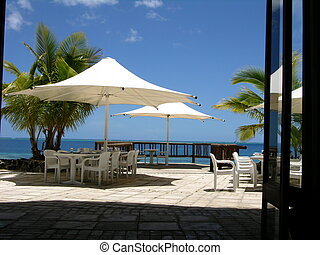 Tropical Lunchtime - quiet seaside cafe patio with palm...
