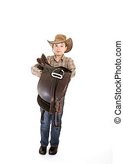Boy carrying a saddle - Boy holding a leather saddle in his...