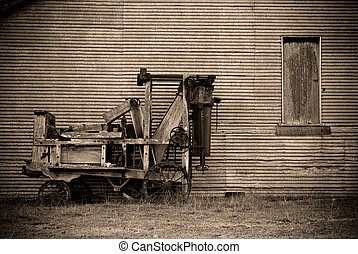 old baler - an old baler in front of a barn on the farm in...