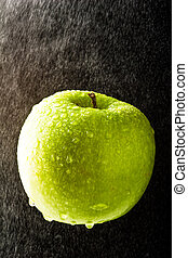 Green Apple with waterdrops on black background