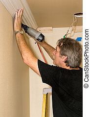 Installing Crown Moulding - carpenter installing crown...