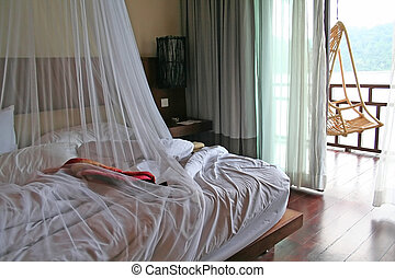 Tropical bed with mosquito netting and balcony