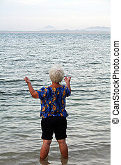 Woman wading in the water, arms out relaxing