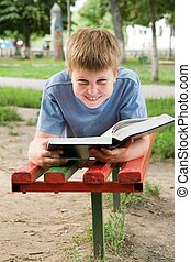 schoolboy reads the book on a bench in park