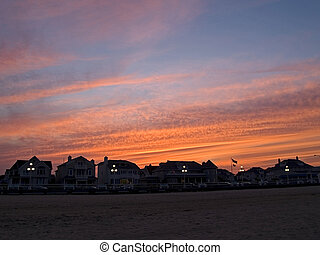 Beach Homes at Dusk - A dramatic sunset and the dark...