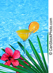 Tropical orange juice by the pool and hibiscus