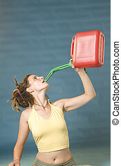 woman drinks of jerry can - a young woman drinks from a red...